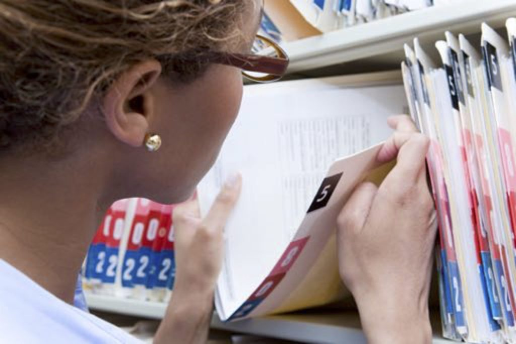 Image of a person putting a file on a shelf to protect its privacy