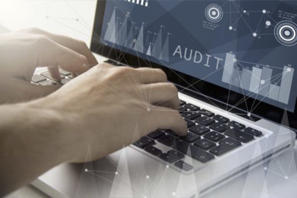 Image of hands at a laptop with the word Audit on the screen
